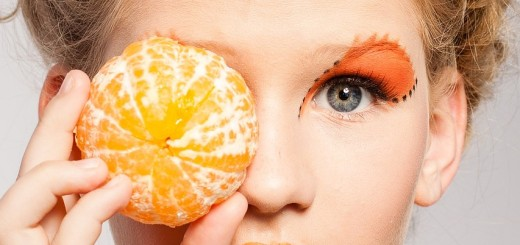 woman with an orange to her eye