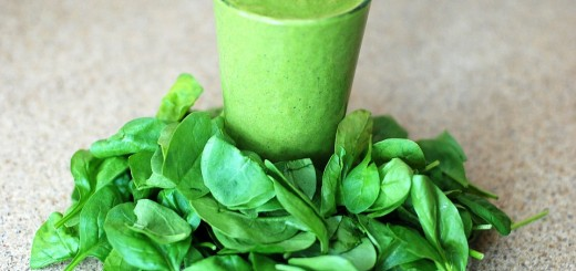 Green smoothie surrounded by leaves
